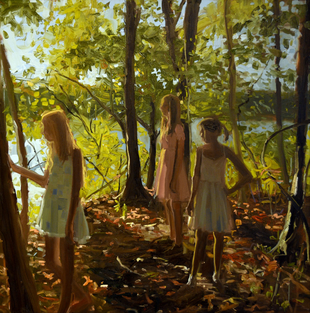 three girls stand on sunlit, wooded lakeshore